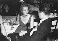 <p>Davis is pictured with an unidentified man during the 9th annual Academy Awards banquet, held at the Biltmore Hotel in Los Angeles.</p>