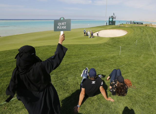 """A Saudi woman wearing Islamic """"Niqab"""" raises """"quiet please"""" sign as British Ashley Chesters plays out of a bunker at the 16th hole during the final round of the Saudi International at Royal Greens Golf and Country Club, Sunday, Feb. 2, 2020, in Red Sea resort of King Abdullah Economic City, Saudi Arabia. (AP Photo/Amr Nabil)"""