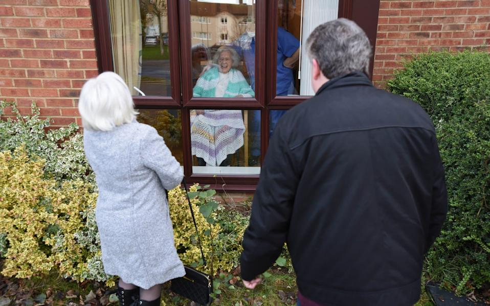 Mary Burns, aged 91, a resident of West Farm Residential Care Centre, Longbenton, Newcastle upon Tyne, talks to her daughter Angela and son John through the window - Asadour Guzelian/Guzelian Ltd