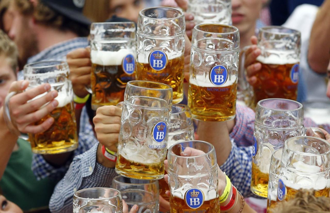 FILE - In this Sept. 19, 2015 file photo, people celebrate the opening of the 182nd Oktoberfest beer festival in Munich, sGermany. Munich's city council has voted down an attempt to cap foaming beer prices at the annual Oktoberfest. Deputy mayor Josef Schmid,who oversees the Bavarian capital's annual beer extravaganza, had sought a legal cap for the next three years on the price of the traditional Mass, a one-liter (two-pint) glass of beer. Schmid failed to secure a majority for his plan at a council meeting Wednesday, May 17, 2017 news agency dpa reported. (AP Photo/Matthias Schrader, file)