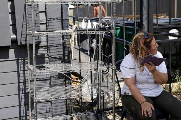 PHOTO: Vanessa Curtis Nosetti charges her phone with others at a charging station set up off a generator at Mayhew Bakery as power continues to be out in most of the city after hurricane Ida ripped through the state, in New Orleans, Sept. 1, 2021. (Leah Millis/Reuters)