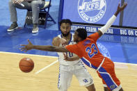 Kentucky's Davion Mintz, left, passes around Florida's Scottie Lewis (23) during the second half of an NCAA college basketball game in Lexington, Ky., Saturday, Feb. 27, 2021. (AP Photo/James Crisp)