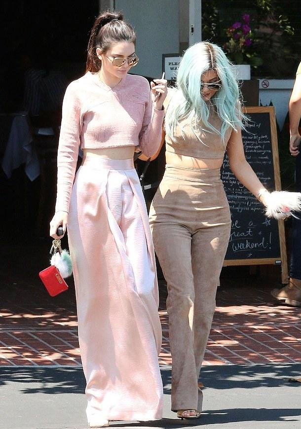 """<p>Sisters that wear crop tops together, stay together. The Jenners hit the streets of Hollywood to shop in coordinated looks. Kendall opted for a pink long sleeved """"shirt"""" by Jonathan Simkhai with a coordinated maxi skirt, while Kylie wore a suede version with matching pants.</p>"""