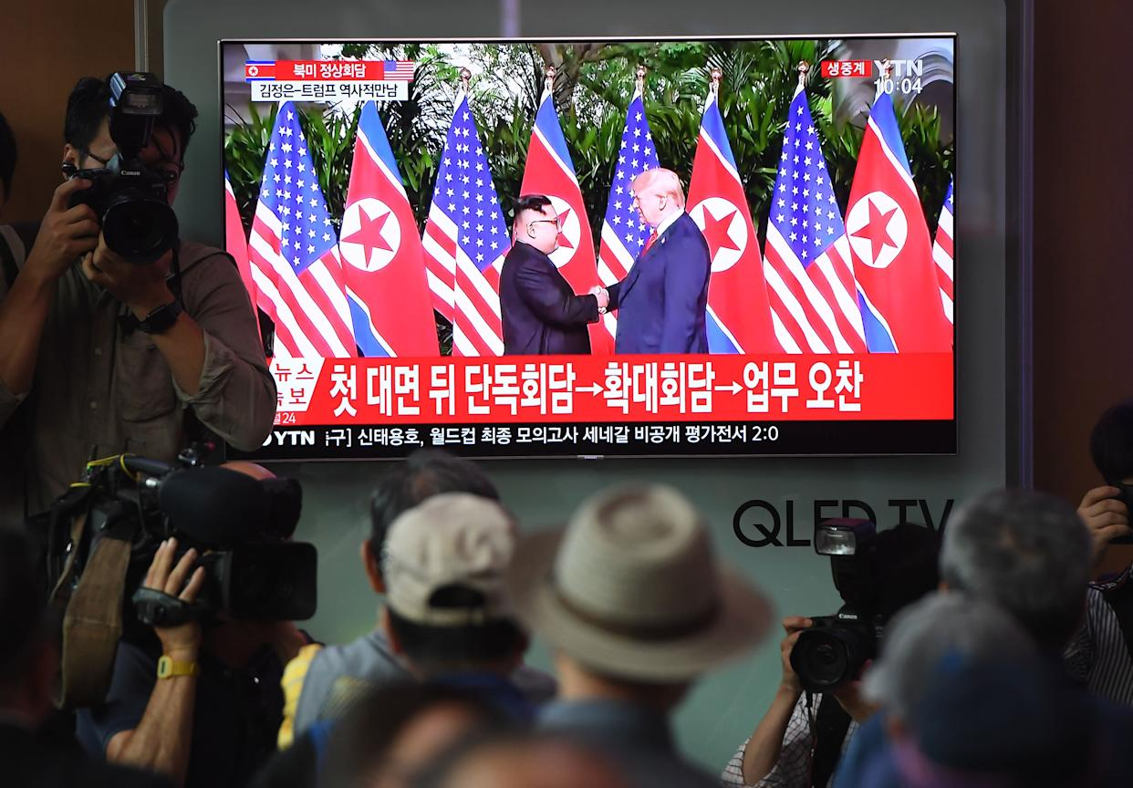 People watch live footage of the handshake between Kim and Trump.