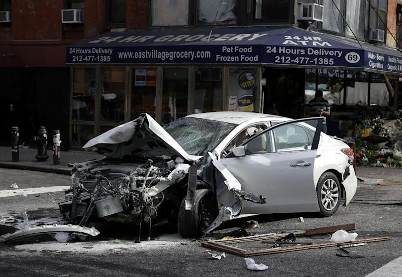 A car damaged in an accident sits in the middle of the street in the East Village section of New York, Wednesday, June 19, 2013. Fire authorities say eight people have been hurt, several of them seriously, after a car jumped a curb and slammed into a 24-hour grocery around 7 a.m. Wednesday. A witness says the driver lost control about a block away and plowed through everything on the sidewalk. (AP Photo/Seth Wenig)