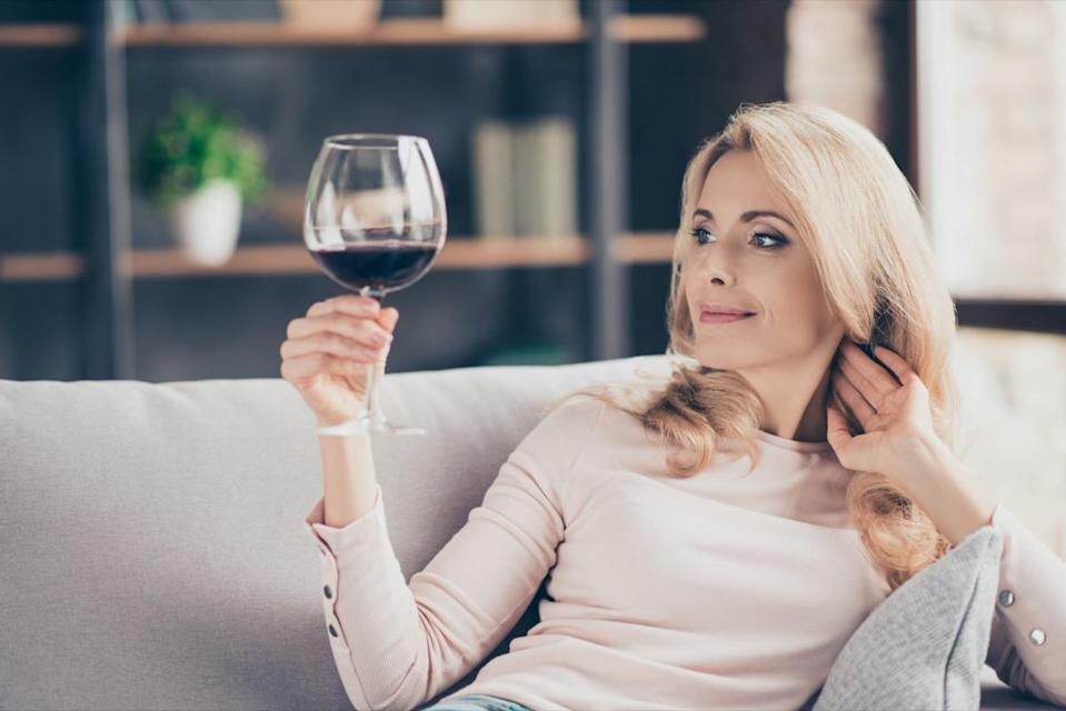 woman sitting on couch having raised glass with red wine in hand