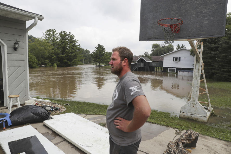 Tyler Statz takes a break from cleaning out his flooded home Tuesday, Aug. 21, 2018, in Black Earth, Wis. Black Earth Creek hit record flood stage with evacuations underway in Black Earth, Cross Plains and Mazomanie, according to Dane County Emergency Management. (Steve Apps/Wisconsin State Journal via AP)