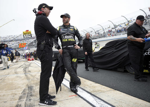Jimmie Johnson, center, talks with crew chief Chad Knaus, left, during a weather delay in the NASCAR Cup series auto race, Sunday, May 6, 2018, at Dover International Speedway in Dover, Del. (AP Photo/Nick Wass)