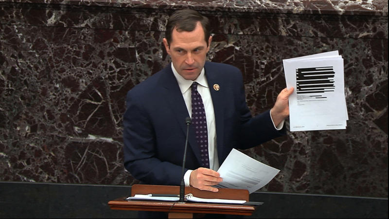In this image from video, House impeachment manager Rep. Jason Crow, D-Colo., holds up documents released by the Office of Management and Budget (OMB) under a Freedom of Information Act request as he speaks during the impeachment trial against President Donald Trump in the Senate at the U.S. Capitol in Washington, Wednesday, Jan. 22, 2020. (Senate Television via AP)