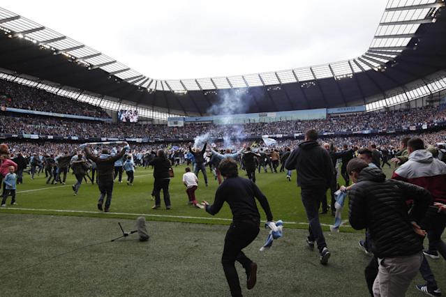 Manchester City fans invade the pitch at the end of their English Premier League soccer match between Manchester City and West Ham at the Etihad Stadium in Manchester, England, Sunday May 11, 2014. Manchester City won the Premier League for the second time in three seasons on Sunday, completing its campaign with a comfortable 2-0 victory over West Ham that lacked any of the drama of its previous title. (AP Photo/Jon Super)