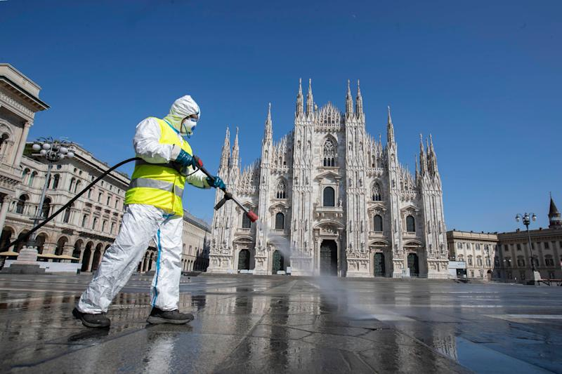 A worker sprays disinfectant to sanitize Duomo square, as the city main landmark, the gothic cathedral, stands out in background, in Milan, Italy, Tuesday, March 31, 2020. The new coronavirus causes mild or moderate symptoms for most people, but for some, especially older adults and people with existing health problems, it can cause more severe illness or death. (AP Photo/Luca Bruno) (Photo: ASSOCIATED PRESS)