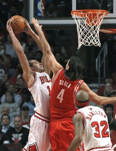 Chicago Bulls center Joakim Noah (13) dunks over Houston Rockets forward Luis Scola (4) as Richard Hamilton watches during the first half of an NBA basketball game Monday, April 2, 2012, in Chicago. (AP Photo/Charles Rex Arbogast)