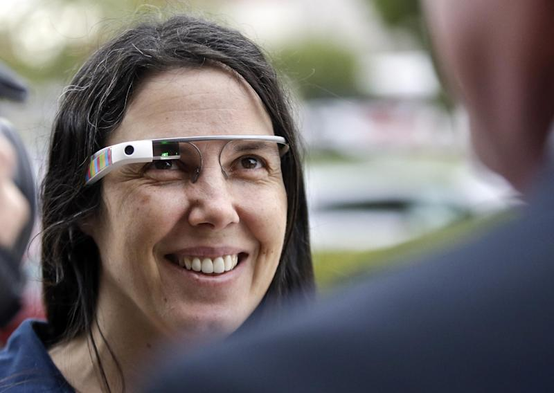 Cecilia Abadie wears her Google Glass as she talks with her attorney outside of traffic court Tuesday, Dec. 3, 2013, in San Diego. When Abadie was pulled over on suspicion of speeding in October, the officer saw she was wearing Google Glass and tacked on a citation usually given to drivers who may be distracted by a video or TV screen. She pleaded not guilty to both charges on Tuesday. (AP Photo/Lenny Ignelzi)