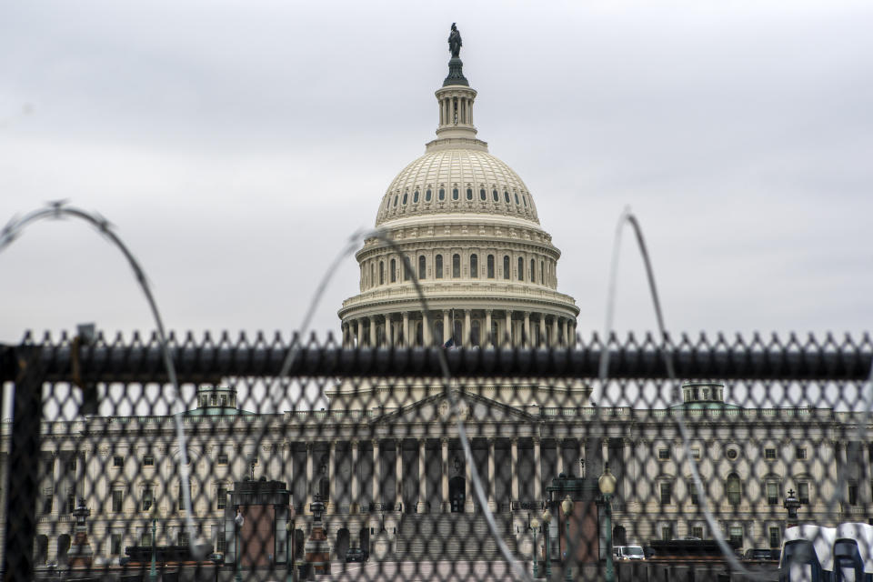 The U.S. Capitol is seen through a fence with barbed wire during the second impeachment trial of former President Donald Trump in Washington, Friday, Feb. 12, 2021. (AP Photo/Jose Luis Magana)