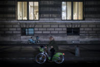 A woman rides a bike as she passes by the Louvre museum during curfew in Paris, Saturday, Oct. 17, 2020. French restaurants, cinemas and theaters are trying to figure out how to survive a new curfew aimed at stemming the flow of record new coronavirus infections. The monthlong curfew came into effect Friday at midnight, and France is deploying 12,000 extra police to enforce it. (AP Photo/Lewis Joly)