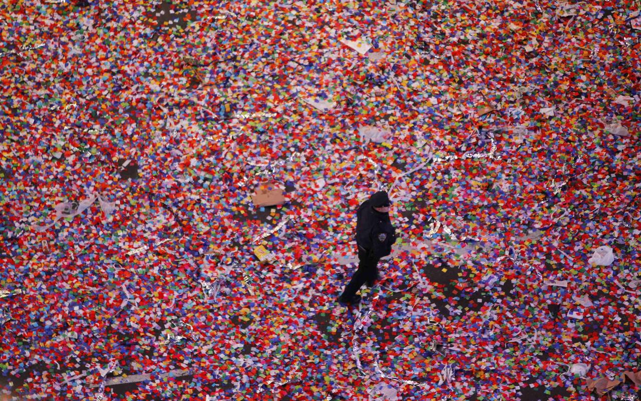 A policeman walks through confetti after it was dropped on revelers at midnight during New Year's Eve celebrations in Times Square in New York January 1, 2014. REUTERS/Gary Hershorn (UNITED STATES - Tags: SOCIETY)