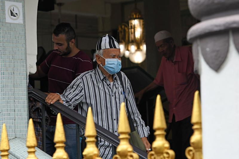 A man wearing a protective facemask amid fears about the spread of the COVID-19 coronavirus leaves a mosque after Friday prayer in Singapore on February 21, 2020. (Photo by ROSLAN RAHMAN / AFP) (Photo by ROSLAN RAHMAN/AFP via Getty Images)