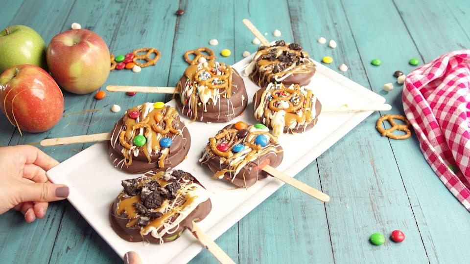 """<p>These snackable caramel-apple slices are topped with all the greats.</p><p>Get the recipe from <a href=""""https://www.delish.com/cooking/recipe-ideas/recipes/a49258/chocolate-apple-pops-recipe/"""" rel=""""nofollow noopener"""" target=""""_blank"""" data-ylk=""""slk:Delish"""" class=""""link rapid-noclick-resp"""">Delish</a>.</p>"""