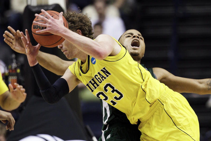 Michigan forward Evan Smotrycz (23) collides with Ohio forward Reggie Keely in the second half of a second-round NCAA college basketball tournament game on Friday, March 16, 2012, in Nashville, Tenn. Ohio won 65-60. (AP Photo/Mark Humphrey)