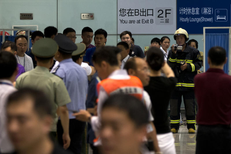 A paramilitary policeman in fire suit takes videos of the area where a man on a wheelchair set off a homemade bomb at Terminal 3 of the Beijing International Airport in Beijing, China, Saturday, July 20, 2013. (AP Photo/Alexander F. Yuan)