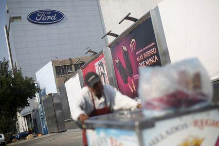 A man selling ice cream man pushes his cart in front of a Ford sales store in Mexico City, Mexico, April 5, 2016. REUTERS/Edgard Garrido