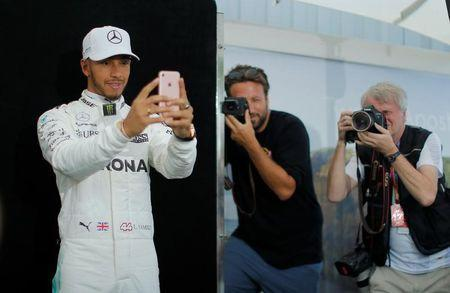 Formula One - F1 - Australian Grand Prix - Melbourne, Australia - 23/03/2017 Mercedes driver Lewis Hamilton of Britain takes a selfie during the driver portrait session at the first race of the year. REUTERS/Jason Reed