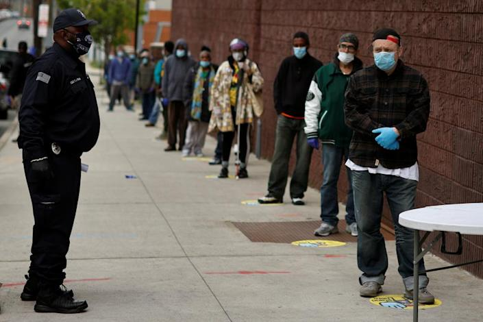 """<span class=""""element-image__caption"""">People stand in line to receive bags containing meals, face masks and other personal protective supplies for residents in need in Newark, New Jersey.</span> <span class=""""element-image__credit"""">Photograph: Mike Segar/Reuters</span>"""