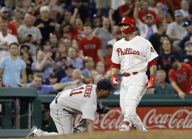 Philadelphia Phillies' Wilson Ramos, right, reacts near Boston Red Sox third baseman Rafael Devers after Ramos hit a triple during the sixth inning of a baseball game Wednesday, Aug. 15, 2018, in Philadelphia. Philadelphia won 7-4. (AP Photo/Matt Slocum)