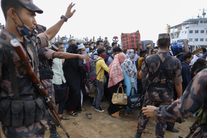 Bangladeshi border guards try to control crowd as thousands of people leaving for their native places to celebrate Eid-al-Fitr throng the Mawa ferry terminal ignoring risks of coronavirus infection in Munshiganj, Bangladesh, Thursday, May 13, 2021. (AP Photo/Mahmud Hossain Opu)