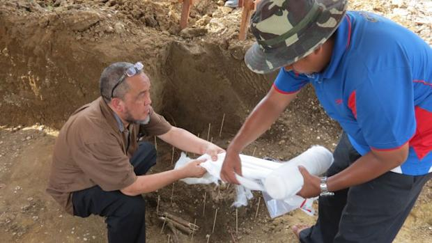 Prof Datuk Mokhtar Saidin (left) at the excavation site in Guar Kepah after the discovery of the skeleton.