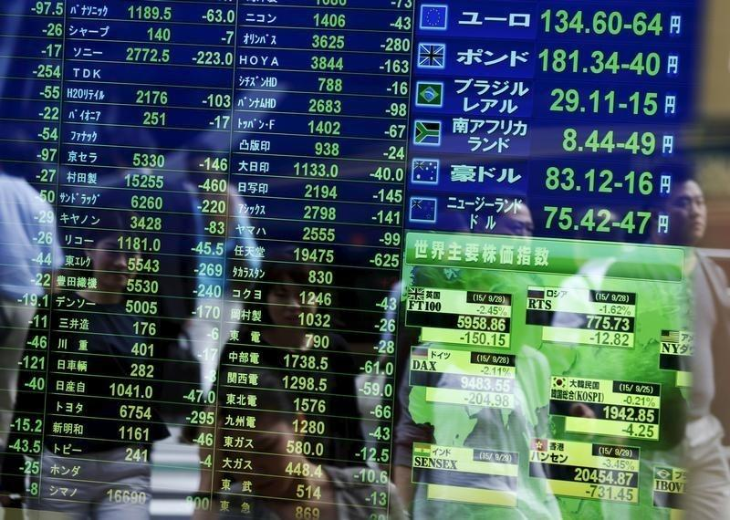 Passersby are reflected on a screen displaying stock quotation, the stock market indices of various countrie and exchange rates at a brokerage in Tokyo