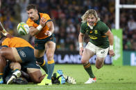Australia's Nic White passes the ball as South Africa's Faf de Klerk chases during the Rugby Championship test match between the Springboks and the Wallabies in Brisbane, Australia, Saturday, Sept. 18, 2021. (AP Photo/Tertius Pickard)