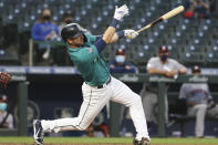 Seattle Mariners' Mitch Haniger singles on a line drive during the third inning of the team's baseball game against the Houston Astros on Friday, April 16, 2021, in Seattle. (AP Photo/Jason Redmond)