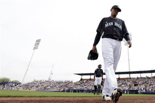 Seattle Mariners starting pitcher Felix Hernandez, right, leaves the field followed by catcher Jesus Montero at the end of the third inning while playing the Los Angeles Dodgers in an exhibition spring training baseball gam,e Wednesday, March 27, 2013, in Peoria, Ariz. (AP Photo/Gregory Bull)