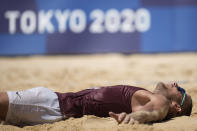 Edgars Tocs, of Latvia, lies in the sand as he celebrates winning a men's beach volleyball quarterfinal match against Brazil at the 2020 Summer Olympics, Wednesday, Aug. 4, 2021, in Tokyo, Japan. (AP Photo/Felipe Dana)
