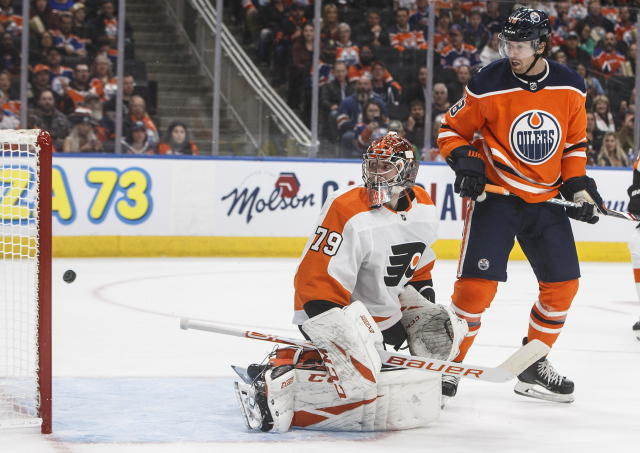 Philadelphia Flyers goalie Carter Hart (79) and Edmonton Oilers' James Neal (18) watch the puck go in for an Edmonton goal during the second period of an NHL hockey game Wednesday, Oct. 16, 2019, in Edmonton, Alberta. (Jason Franson/The Canadian Press via AP)