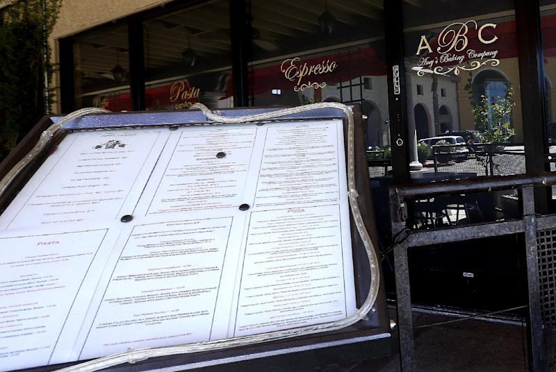 """This Monday, June 3, 2013 photo shows Amy's Baking Company in Scottsdale, Ariz., with the menu displayed outside the restaurant. The restaurant temporarily closed after their """"Kitchen Nightmares"""" episode aired. The episode of """"Kitchen Nightmares"""" drew more than a million viewers on YouTube, and restaurateur Amy Bouzaglo's vitriolic rants became popular fodder on Twitter and Facebook. Bouzaglo announced she is shopping around her own reality TV show. (AP Photo/Ross D. Franklin)"""