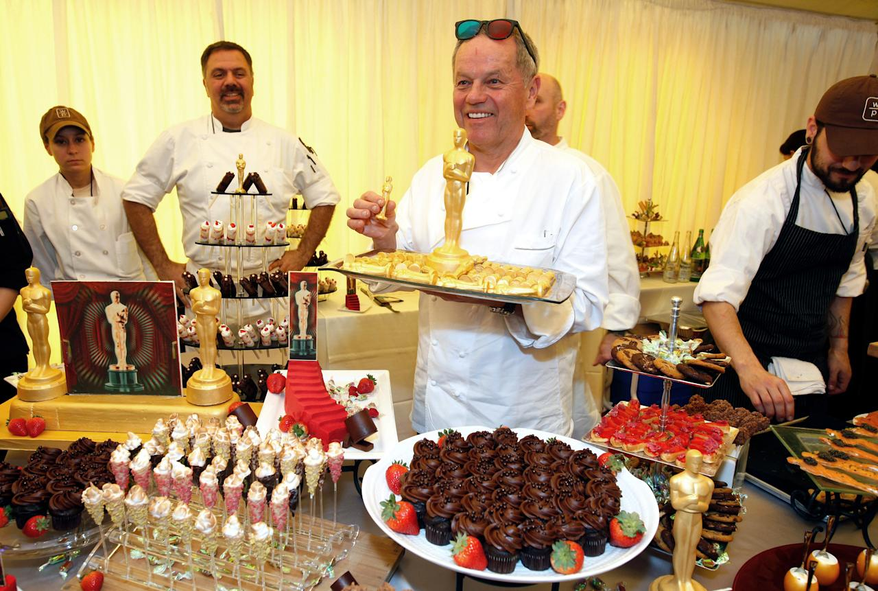 Master Chef Wolfgang Puck, center, holds a tray of 24-karat chocolate Oscars for the 84th Annual Academy Awards Governors Ball at the Oscar food and beverage preview at the Kodak Theatre in Los Angeles on Thursday, Feb. 23, 2012. (AP Photo/Damian Dovarganes)