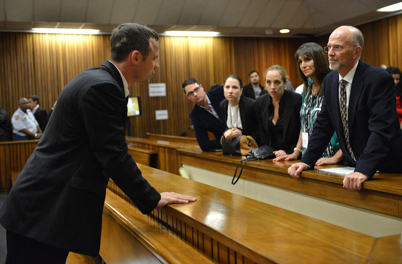 Oscar Pistorius, talks with his uncle Arnold Pistorius, right, inside court on the second day of his trial at the high court in Pretoria, South Africa, Tuesday, March 4, 2014. Pistorius is charged with murder for the shooting death of his girlfriend, Reeva Steenkamp, on Valentines Day in 2013. (AP Photo/Antoine de Ras, Pool)
