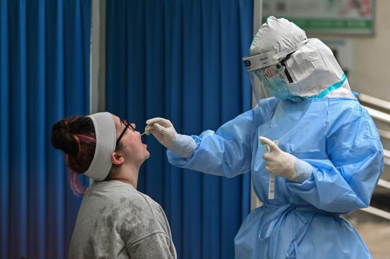 A new cluster of cases has sparked mass coronavirus testing in the central Chinese city of Wuhan (AFP Photo/Hector RETAMAL)