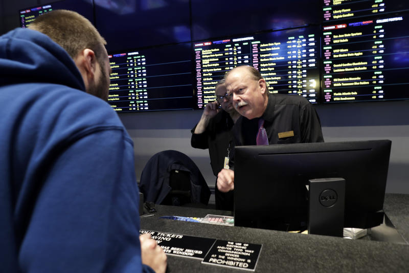In this Nov. 18, 2019, photo, Sportsbook shift manager Stuart Norsell, right, assists a patron, left, in the sports betting area of Twin River Casino in Lincoln, R.I. Legalized sports betting's rapid march across the U.S. could face some bigger tests in 2020. Less than two years after a U.S. Supreme Court ruling opened the door to sportsbooks outside Nevada, they have been legalized in states that are home to about one-third of the nation's population. (AP Photo/Steven Senne)