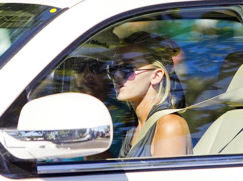 """FILE - In this Jan. 11, 2013, file photo, Paulina Gretzky, right, and Dustin Johnson drive away from the Waialae Country Club after Johnson withdrew from the Sony Open Golf Tournament after playing nine holes in the second round in Honolulu. PGA Tour player Johnson and Gretzky have taken to Twitter to say they are getting married. Johnson tweeted Sunday, Aug. 18, 2013, that """"she said yes!!!"""" and included a picture of a large diamond ring on the daughter of hockey great Wayne Gretzky. (AP Photo/Marco Garcia, File)"""