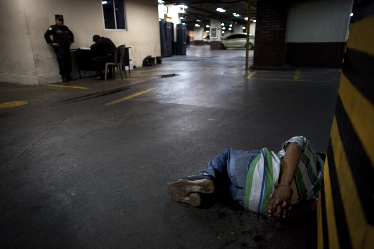 In this picture taken Thursday Jan. 26, 2012, a man lies handcuffed in a court parking lot after being detained in Guatemala City. President Otto Pérez Molina will meet on Monday with El Salvador's President Mauricio Funes to address issues related to regional security and how to coordinate their fight against organized crime. Perez has blamed the drug cartels for the high levels of violence in his country of 13 million overrun by gangs and the Mexican cartels, with a rate of 41 homicides per 100,000 inhabitants, nearly three times that of neighboring Mexico. (AP Photo/Rodrigo Abd)
