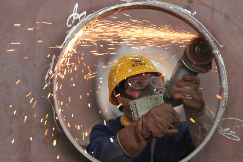 FILE PHOTO: Employee works on a production line manufacturing steel structures at a factory in Huzhou