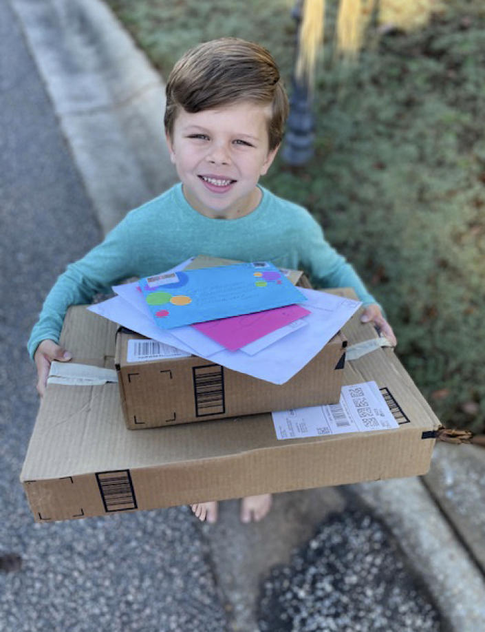 Chip Matthews, 6, holds a stack of birthday presents delivered to his home in Opelika, Ala., on Thursday, Nov. 5, 2020. Matthews was given an extra birthday surprise when postal worker, Tawanna Purter, gave him $2 as a gift. (Bonnie Matthews via AP)