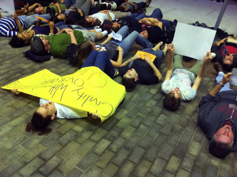 "A group participates in a ""lie-in"" near the Student Center at Rutgers University, in New Brunswick, N.J. The rally was in support of safe places for gay students, in response to the death of a Rutgers University freshman who jumped off a bridge last week after a recording of him having a sexual encounter with a man was broadcast online.  (AP Photo/Erin Vanderbeg)"