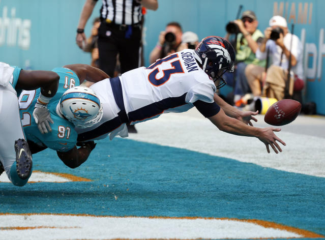 <p>Denver Broncos quarterback Trevor Siemian (13) fumbles the ball as he is tackled by Miami Dolphins defensive end Cameron Wake (91) for safety score, during the first half of an NFL football game, Sunday, Dec. 3, 2017, in Miami Gardens, Fla. (AP Photo/Wilfredo Lee) </p>