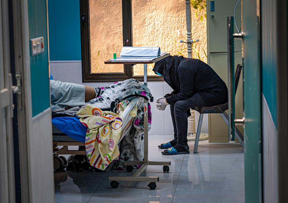 <p>A woman anxiously waits for news on her critically ill husband's condition</p> (Bel Trew)