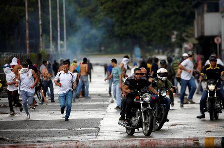 FILE PHOTO: Demonstrators run and ride their motorcycles near Fuerte Paramacay military base during clashes with security forces in Valencia