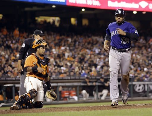 Colorado Rockies' Wilin Rosario, right, scores a run in front of San Francisco Giants catcher Hector Sanchez on a single by Tyler Colvin during the fourth inning of a baseball game in San Francisco, Friday, Aug. 10, 2012. (AP Photo/Tony Avelar)